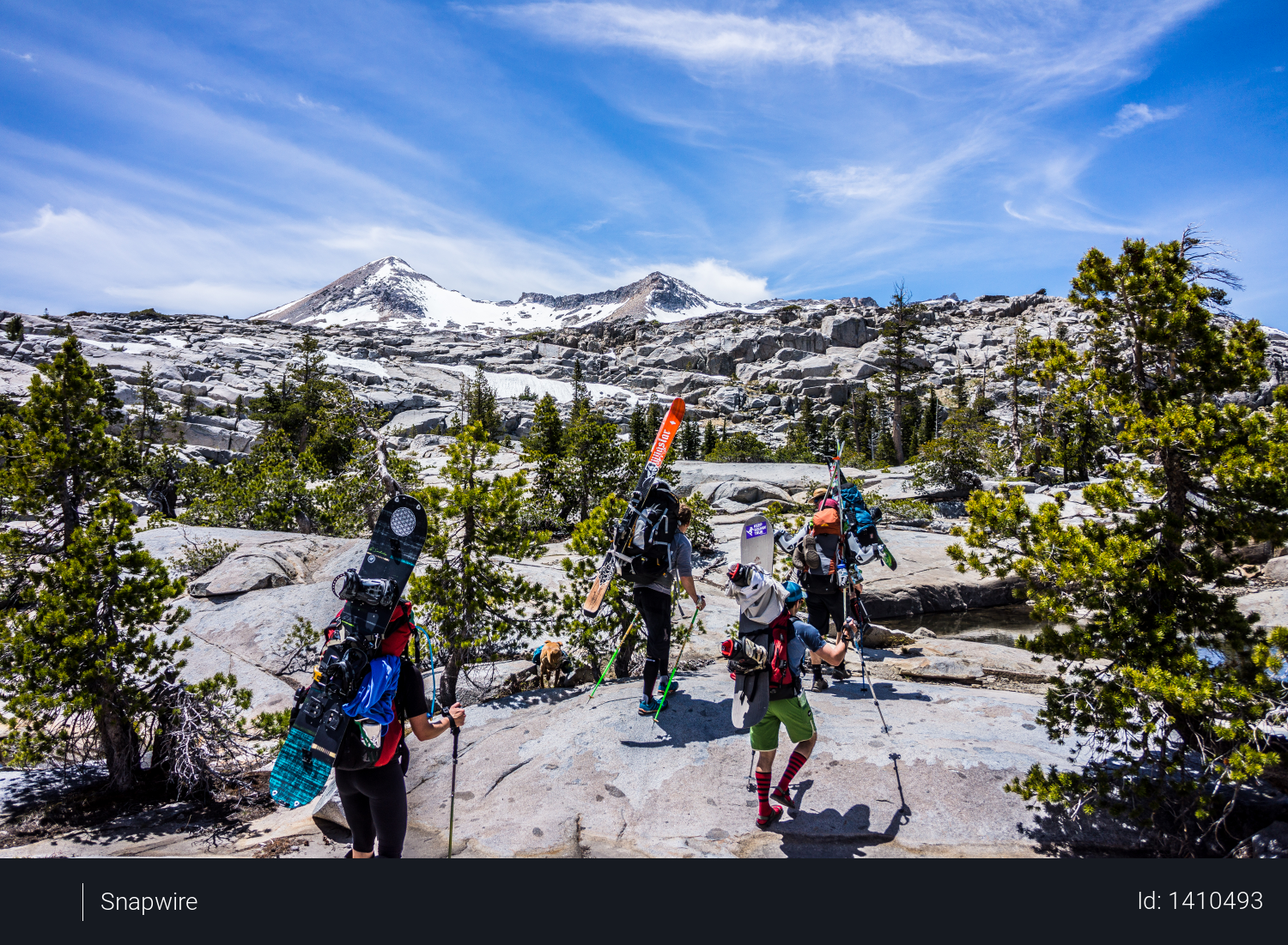 Group of People Hiking With Snowboards Under Blue Cloudy Sky Photo