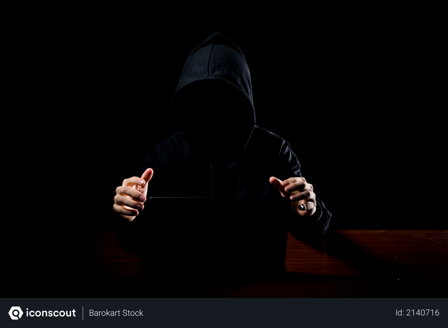 Hacker wearing hoodie with laptop and dark lighting as hacking concept Photo