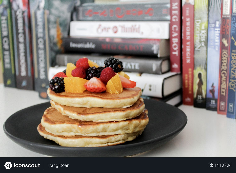 Pancake on Black Plate Near Books Photo