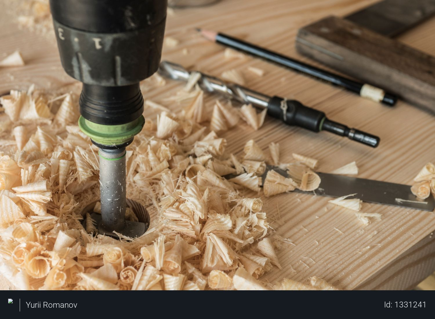 The joiner drills a workpiece of wood with a drill. A drill, a pencil and a corner. chips Photo