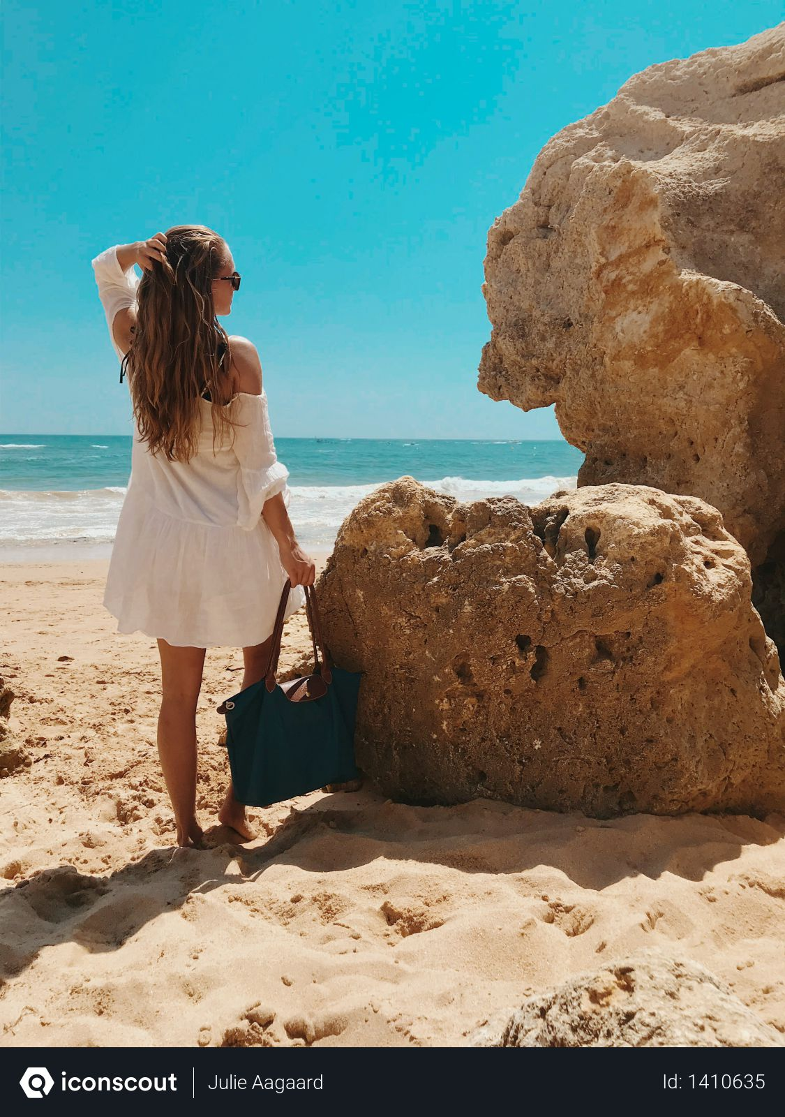 Woman Standing Beside Rocks Near Beach Photo