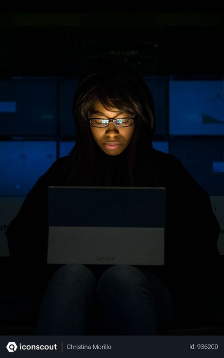 Woman Wearing Eyeglasses Looking At Tablet Computer In Dark Room Photo