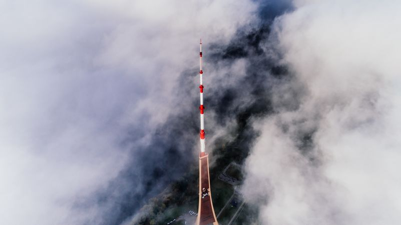 Aerial Photography Of Red And White Striped Tower Near Clouds