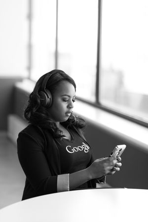 Grayscale Photo Of Woman Holding Smartphone Wearing Wireless Over-ear Headphones