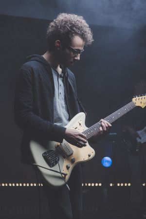 Musician Playing Guitar During Music Concert