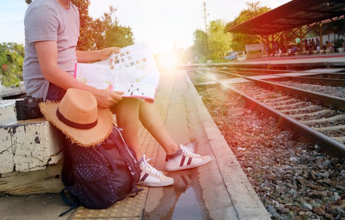 Free Traveler Sitting On Platform With His Map Photo download in PNG & JPG  format