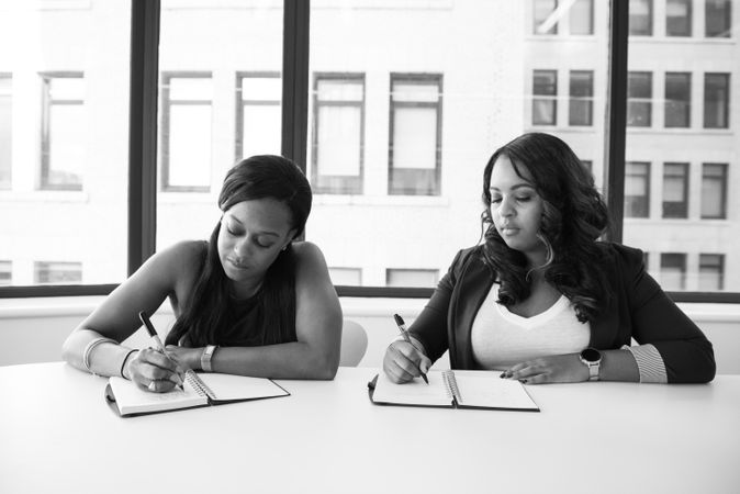 Two Woman Writing Something In Notebook