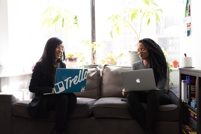 Two Women Sitting On Gray Couch Holding Laptop Computers