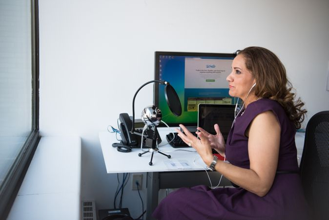 Woman In Purple Sleeveless Dress Sitting In Front Of Pop Filter