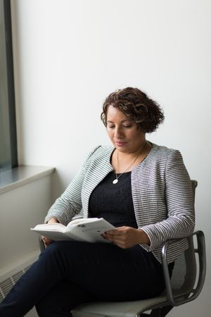 Woman Sitting On Chair And Reading Book
