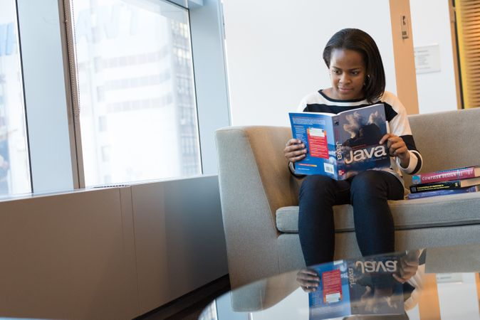 Woman Sitting On Sofa And Read A Java Book