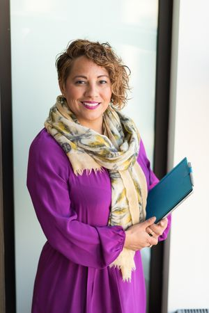 Woman Smiling And Holding Teal Book