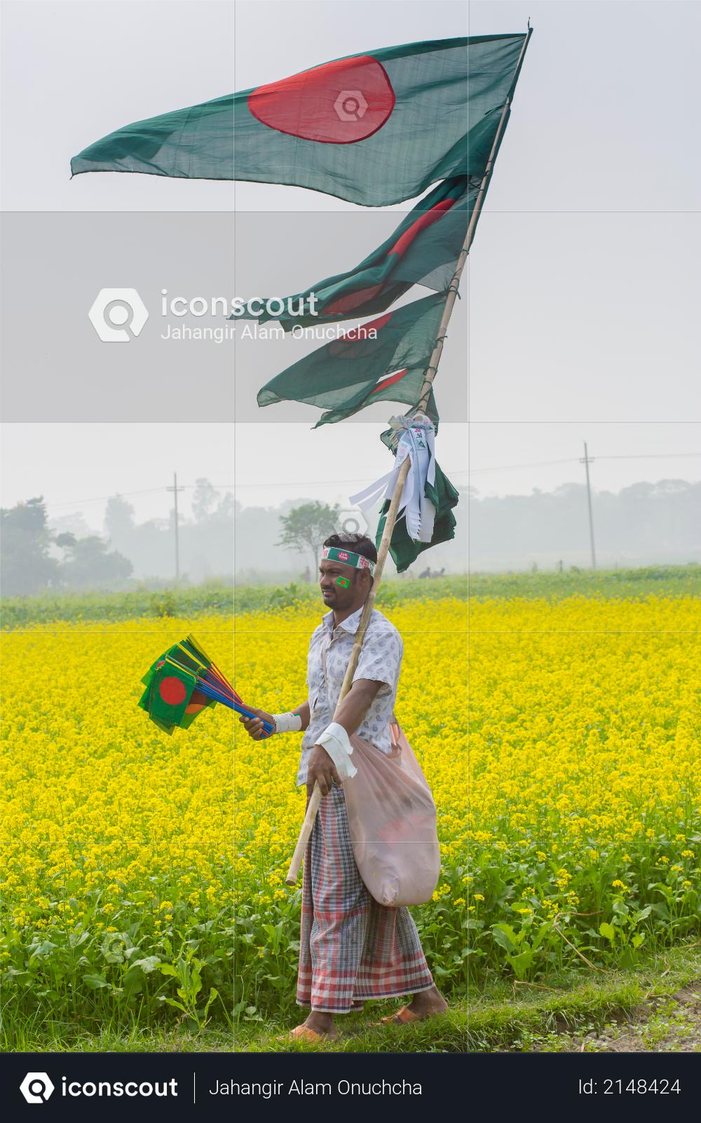 A Hawker sells Bangladeshi national flags at mustard field at Munshigonj, Dhaka, Bangladesh Photo