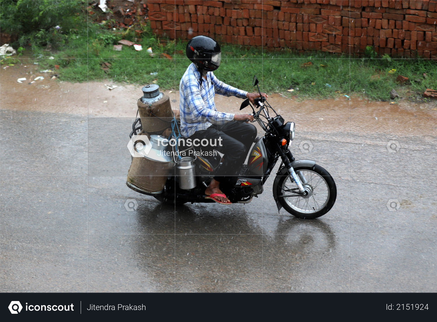 A milkman is riding his motorcycle with milk cans in heavy rain - Monsoon Photo