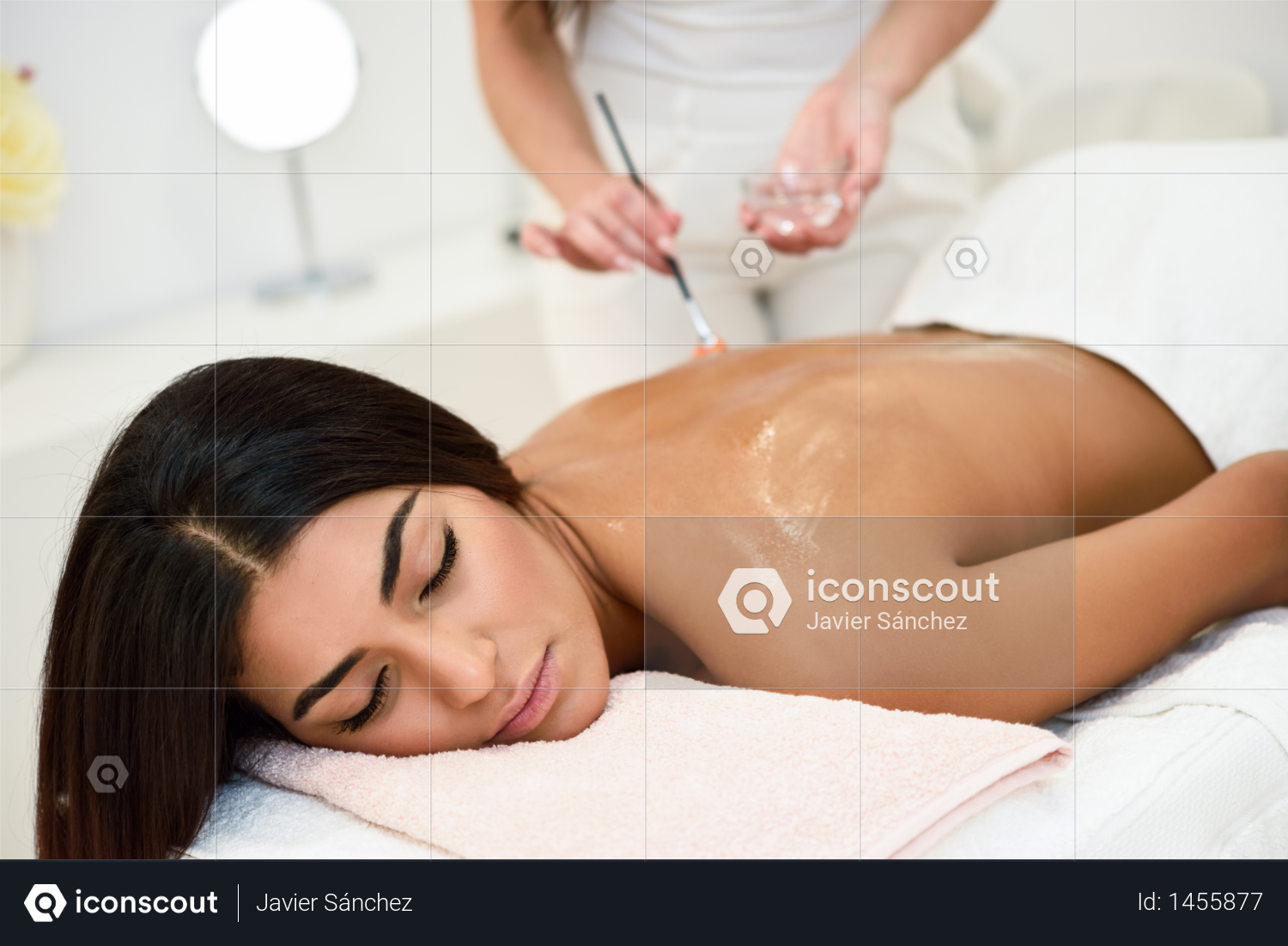 Arab woman receiving back massage treatment with oil brush in spa wellness center. Beauty and Aesthetic concepts. Photo