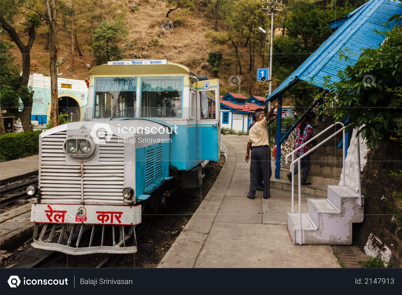 Barog, Himachal Pradesh, India - May 2012: An old passenger Rail Motor car traveling on the narrow gauge railway line between Kalka and Shimla stops at the Barog Railway Station. Photo