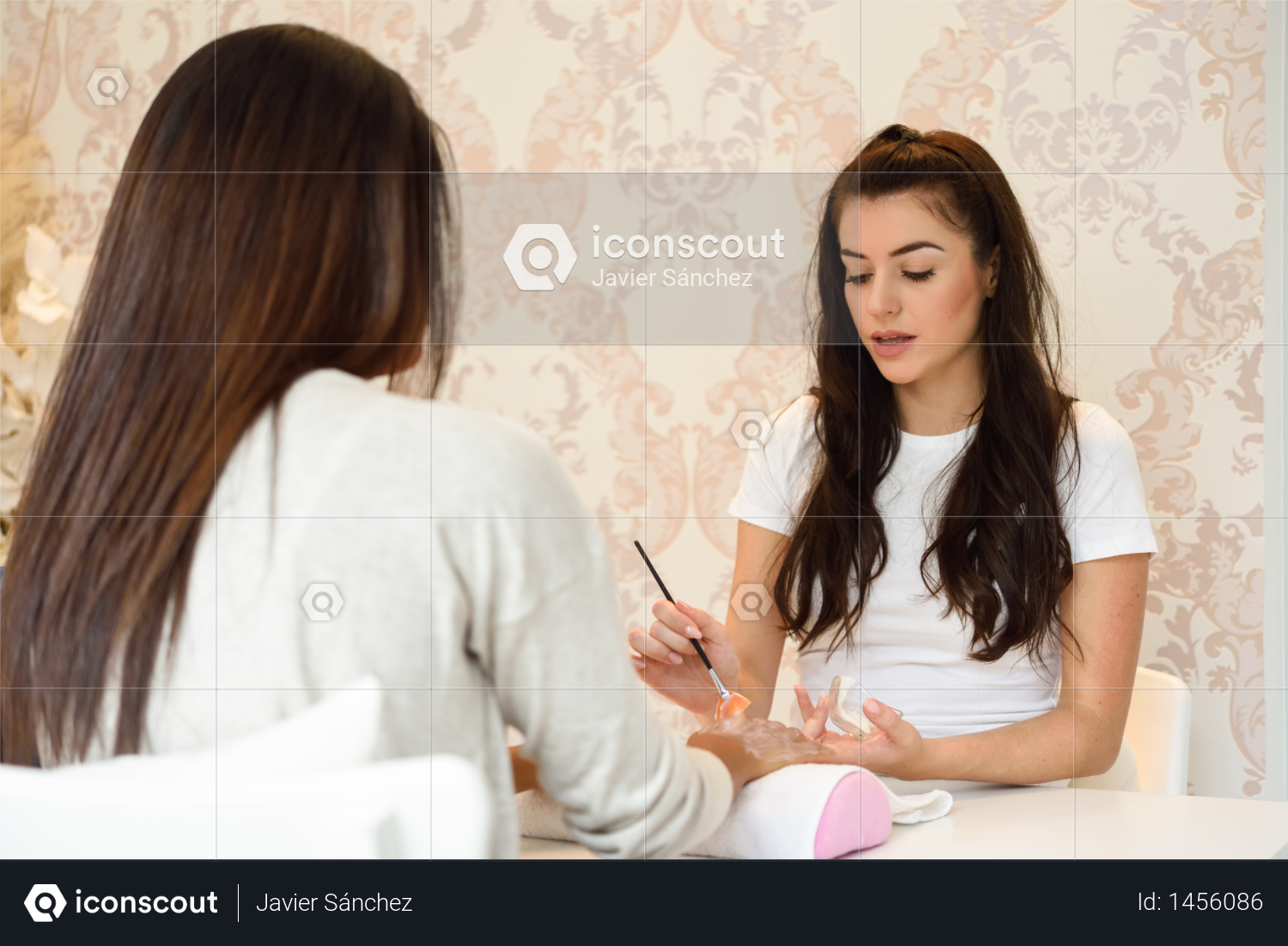 Beautician applying cream on woman's hand using brush. Handcare, taking care of hands, cosmetics concept. Photo
