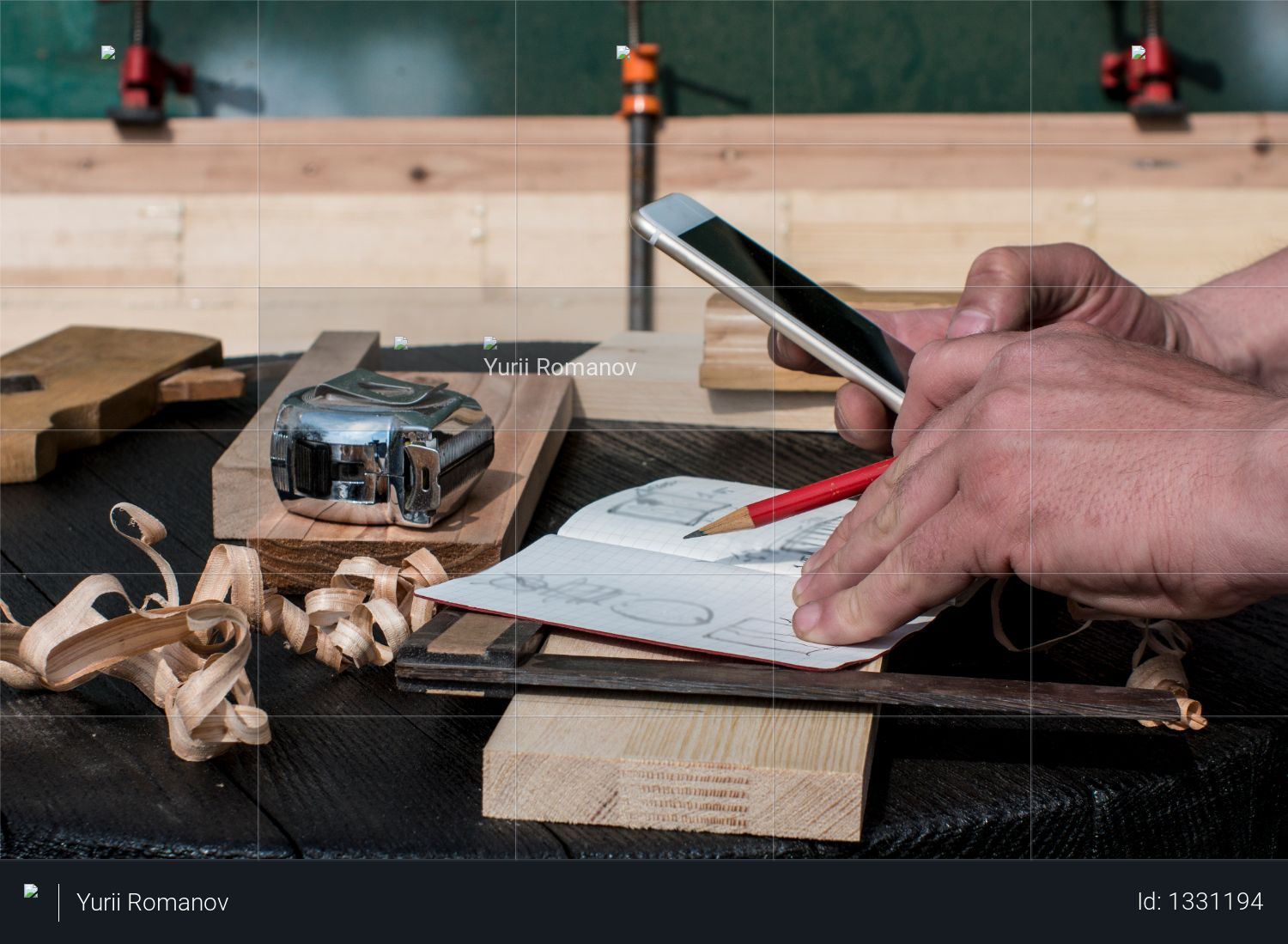 Carpenter in the workshop with a red pencil looking at the blueprints Photo