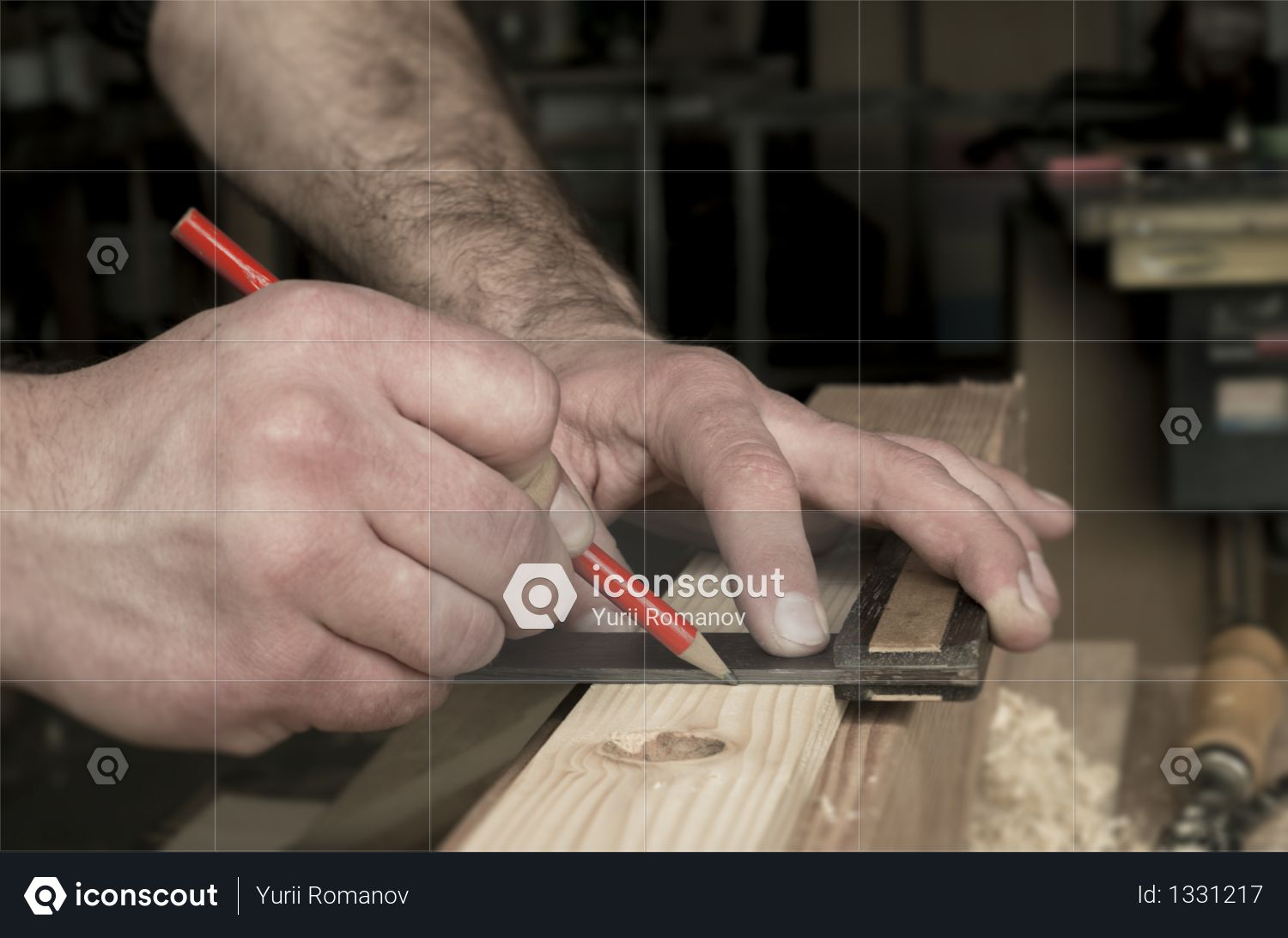 Carpenter marking wooden detail with square and red pencil Photo