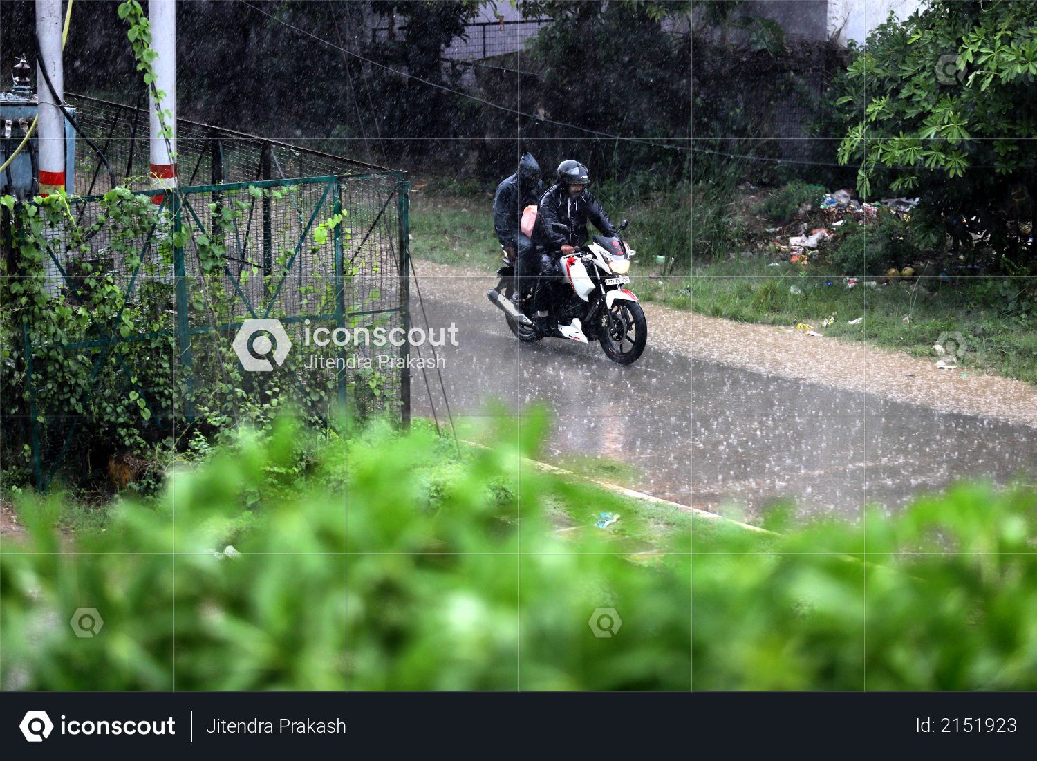 Indian Man in black raincoat & driving bike in rainy day, monsoon Photo