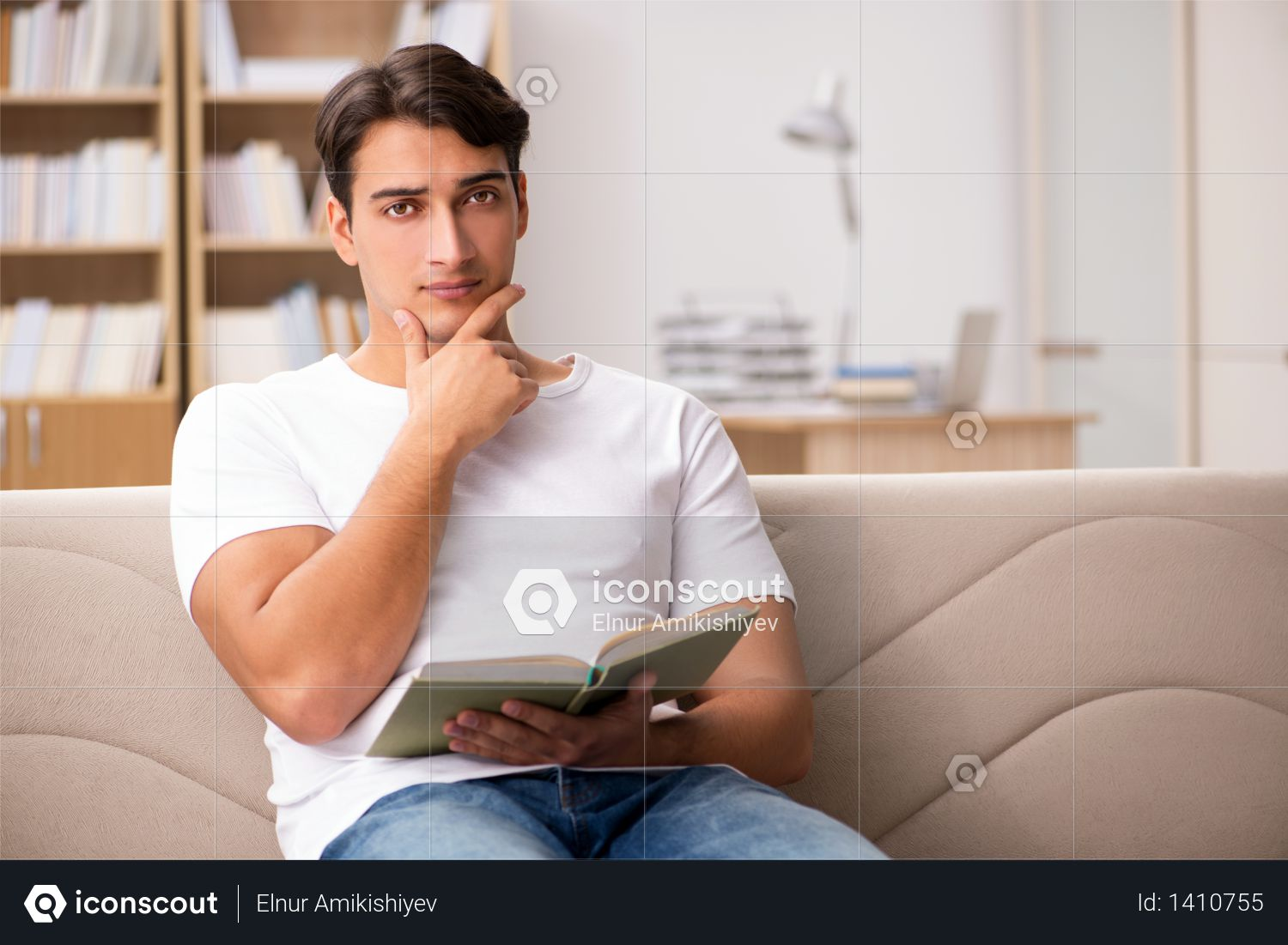 Man reading book sitting in couch sofa Photo