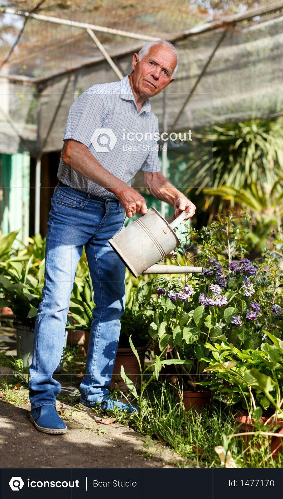 Premium Senior Man Taking Care Of Plants In His Homestead