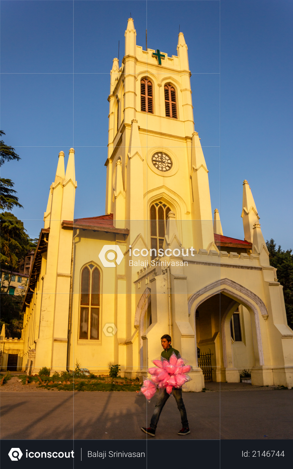Shimla, Himachal Pradesh, India - May 2012: A street vendor walks past the British colonial era neo-Gothic architecture of Christ Church, one of the oldest surviving churches in North India. Photo