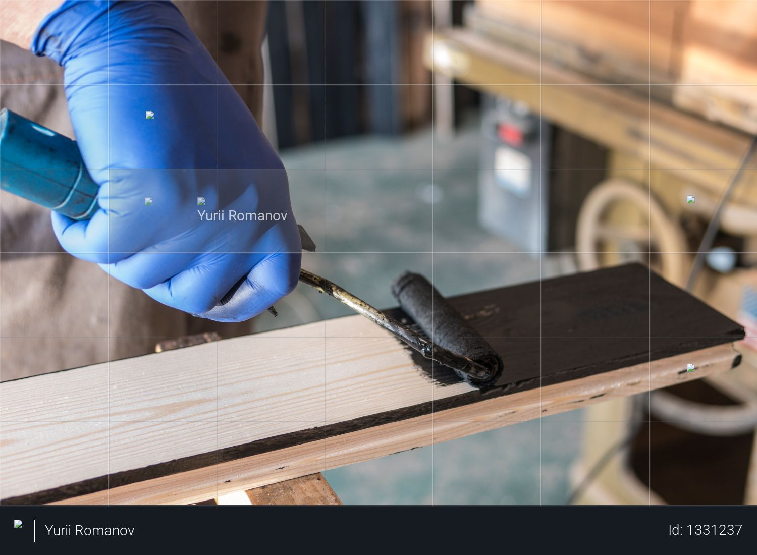 The painter paints black paint with a platen on the board Photo