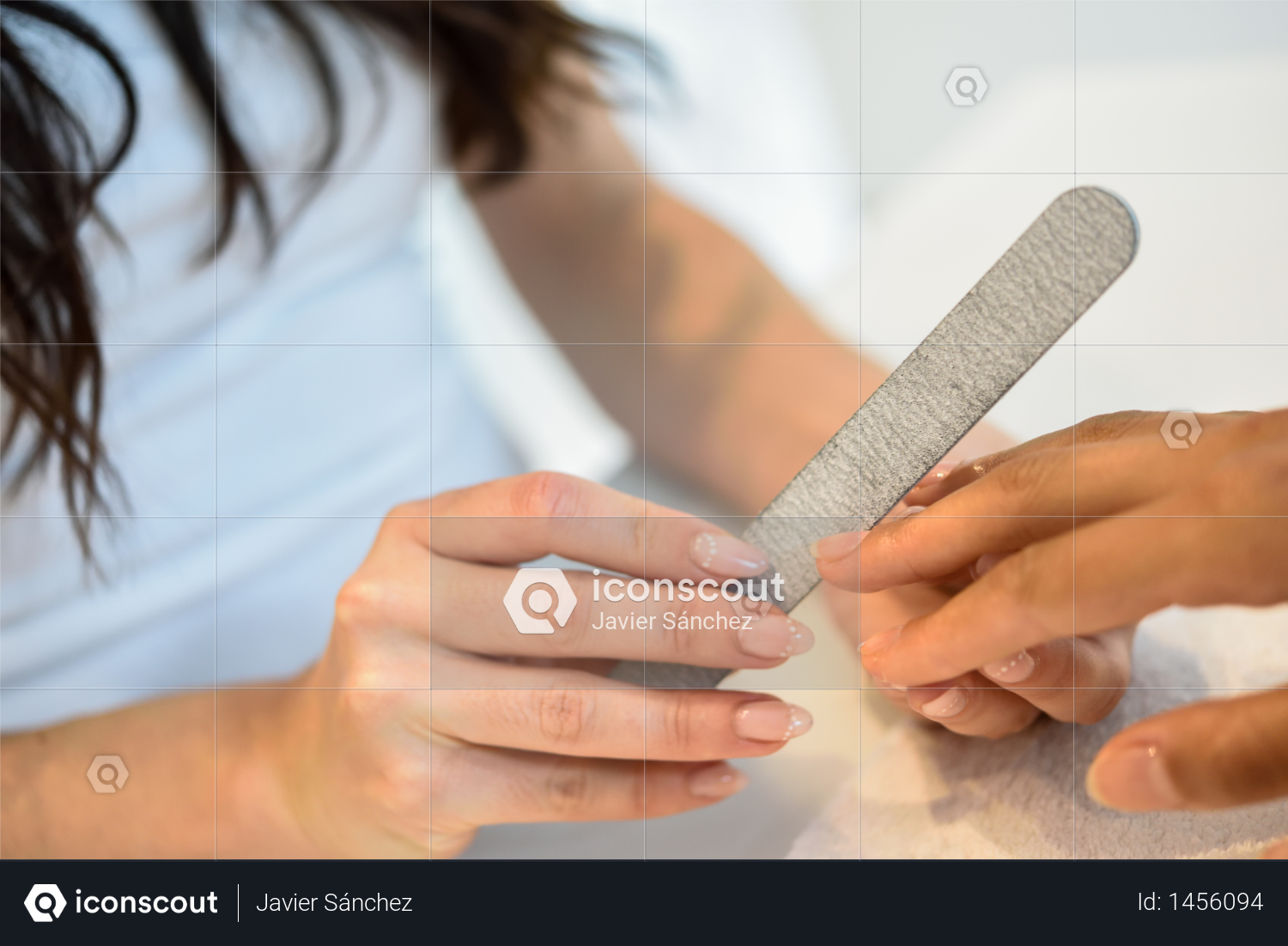 Woman in a nails salon receiving a manicure with nail file Photo