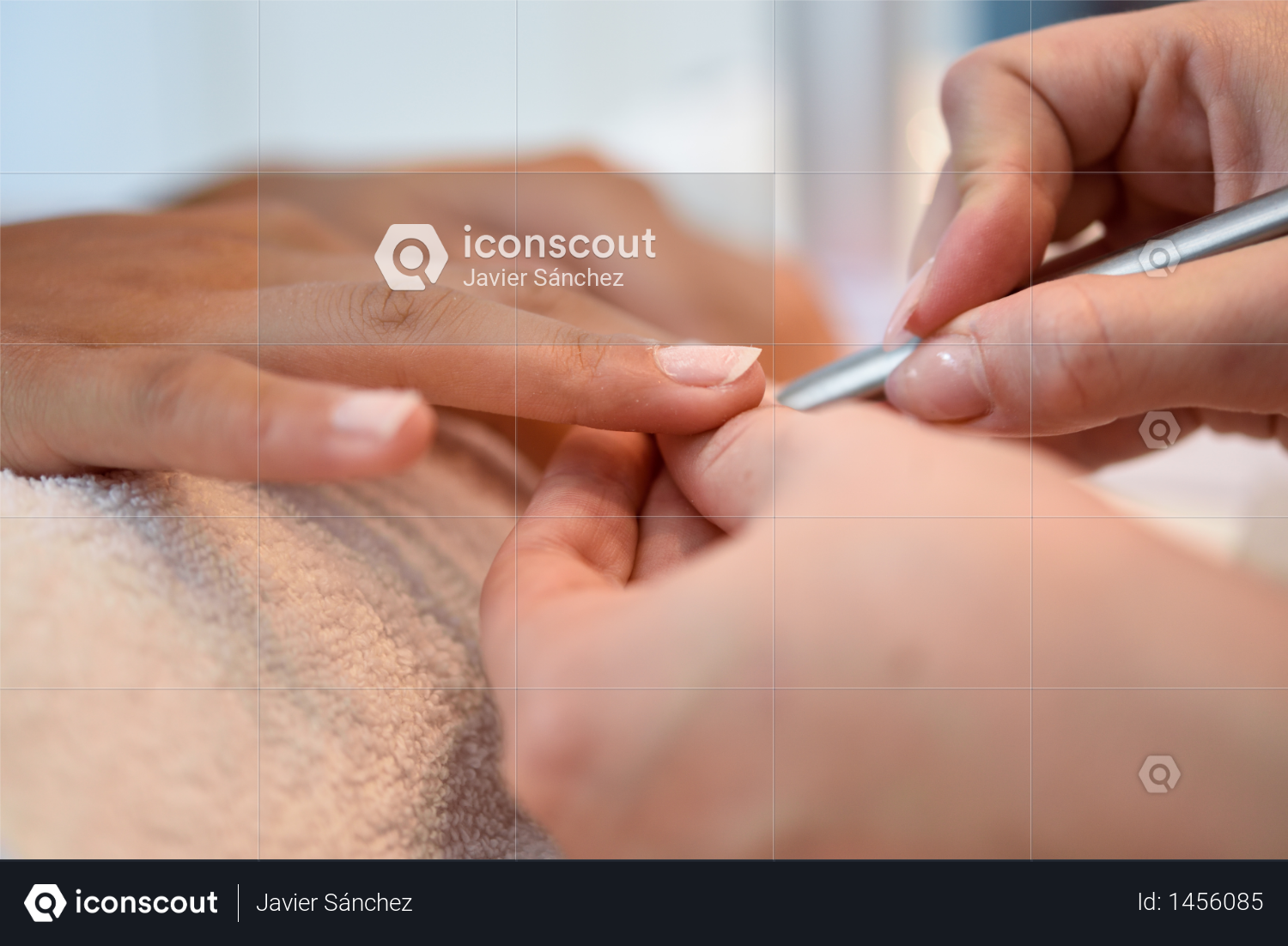 Woman with deteriorated nails in a salon receiving a manicure by a beautician with nail file. Photo