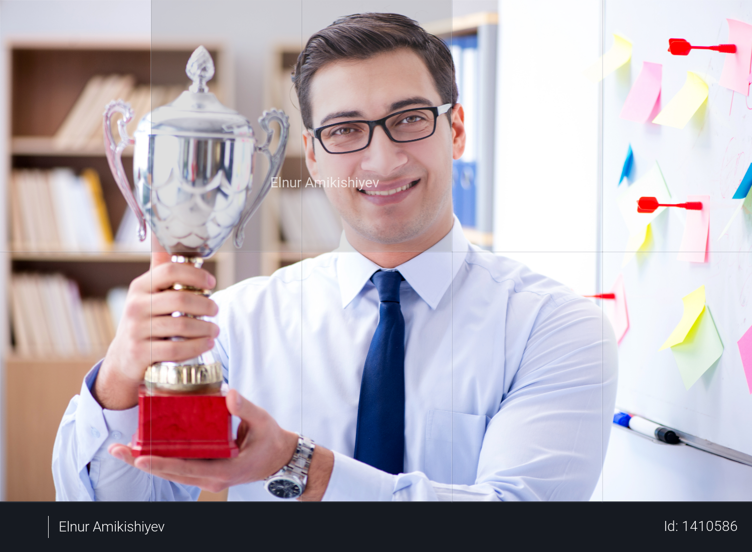 Young businessman receiving prize cup in office Photo