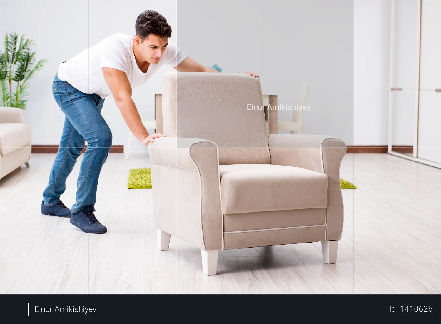 Young man moving furniture at home Photo