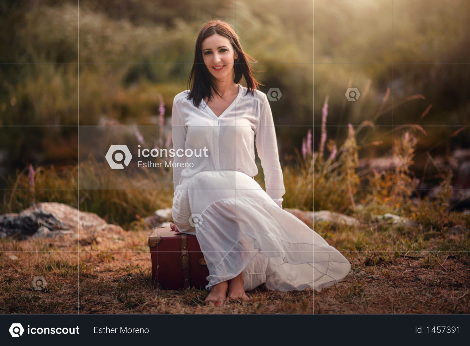 Young woman sitting in the field with suitcase Photo