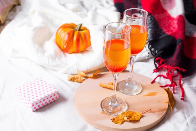 Champagne Pumpkin On A Wooden Board On A Bed With A Blanket And Dry Autumn Leaves