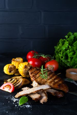 Grilled Steak And Vegetable, Baked Potatoes And Green Salad On Wooden Table