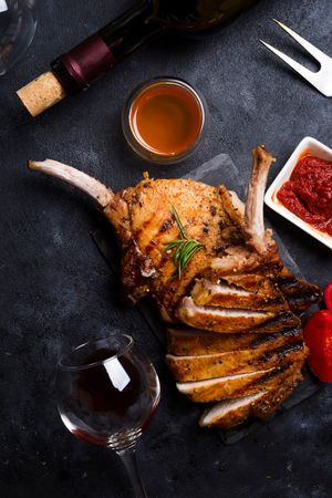 Grilled T-bone Steak With Ketchup, A Glass And A Bottle Of Wine On Stone Table