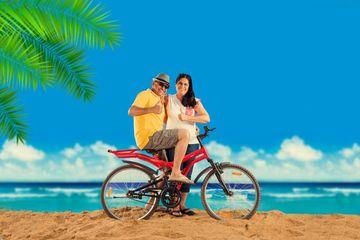 Senior Couple Riding Bicycle At Beach Shoot