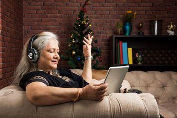 Senior Indian Or Asian Women Listening To Music Using Headphones Shoot