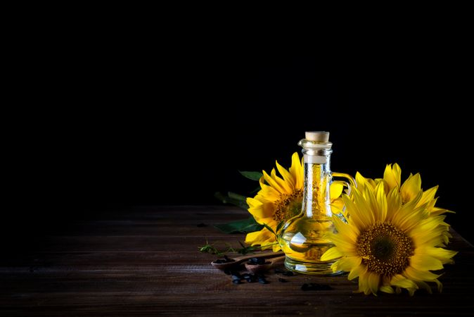 Sunflower Oil In Bottle Glass With Seed And Sunflower On Dark Wooden Table