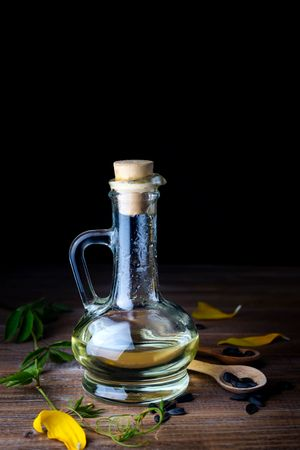 Sunflower Oil In Bottle Glass With Seed On Dark Wooden Table
