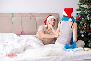Young Happy Family Celebrating Christmas In Bed Shoot